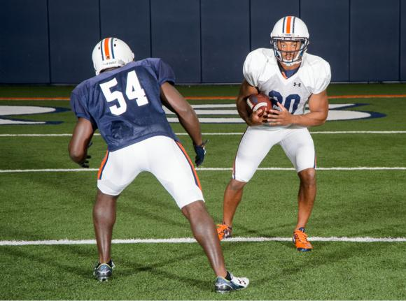 Figure 3.1 Running back uses his head, shoulders, and upper body to juke around a defender.